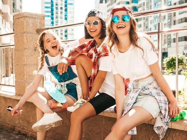 Tres jóvenes sonrientes hermosas chicas con patinetas coloridas centavo.