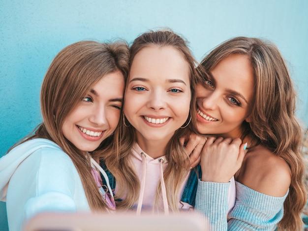 Tres jóvenes sonrientes mujeres hipster en ropa de verano. chicas tomando fotos de autorretrato en smartphone. modelos posando en la calle cerca de la pared. mujeres mostrando emociones positivas.