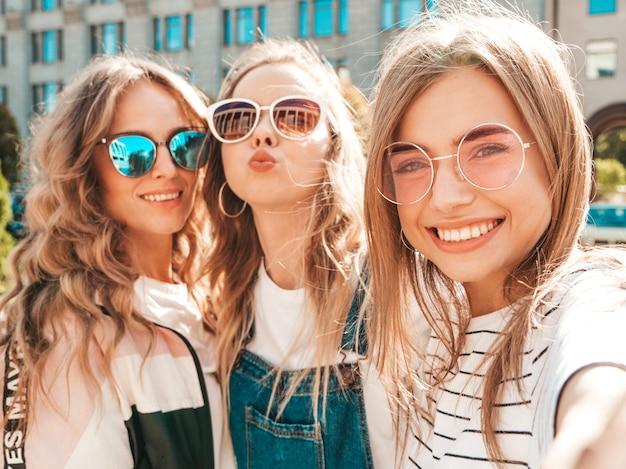 Tres jóvenes sonrientes mujeres hipster en ropa de verano. chicas tomando fotos de autorretrato en smartphone. modelos posando en la calle. mujeres mostrando emociones positivas en la cara.