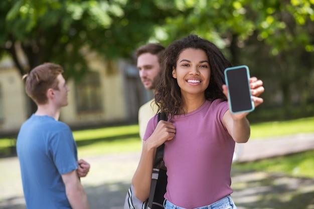 Tres jóvenes con teléfonos inteligentes en las manos, pasar tiempo en el parque