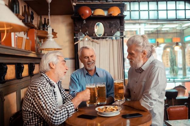 Tres jubilados. tres hombres jubilados de pelo gris comiendo bocadillos y bebiendo cerveza