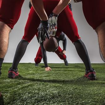 Los tres jugadores de fútbol americano en acción sobre hierba verde y fondo gris.