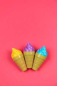 Tres juguetes de helado de plástico sobre fondo rojo.