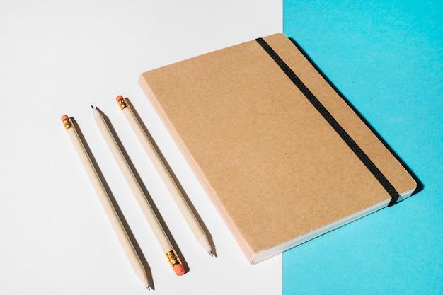 Tres lápices y cuaderno cerrado con tapa marrón.