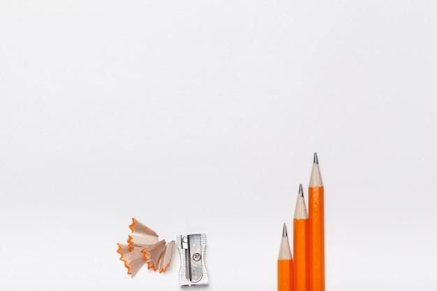 Tres lápices, sacapuntas y virutas de madera aisladas sobre fondo blanco.