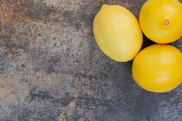 Tres limones enteros frescos en el espacio de mármol.