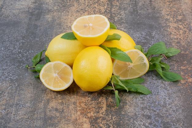 Tres limones frescos enteros con una rodaja en el espacio de mármol
