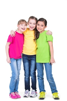 Tres lindas niñas sonrientes lindas en camisetas coloridas de pie - aislados en blanco.