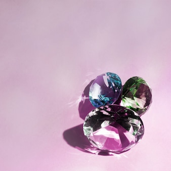 Tres lujosos diamantes brillantes sobre fondo rosa