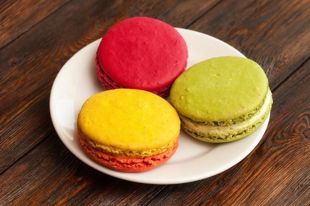 Tres macarons coloridos franceses tradicionales en placa