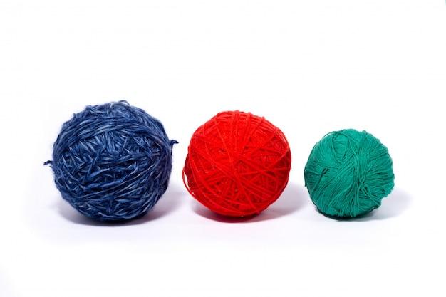 Tres madejas de lana con hilos multicolores aislados en la pared blanca