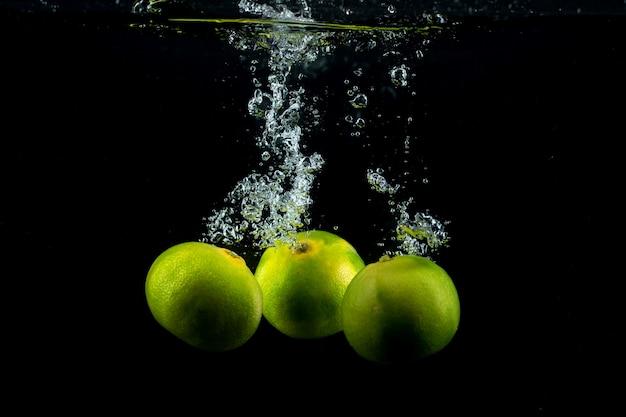 Tres mandarinas verdes en el agua
