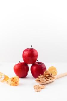 Tres manzanas con cinta métrica y cereales en cuchara.