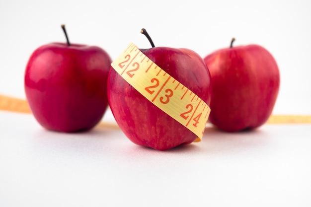 Tres manzanas con cinta métrica en la mesa