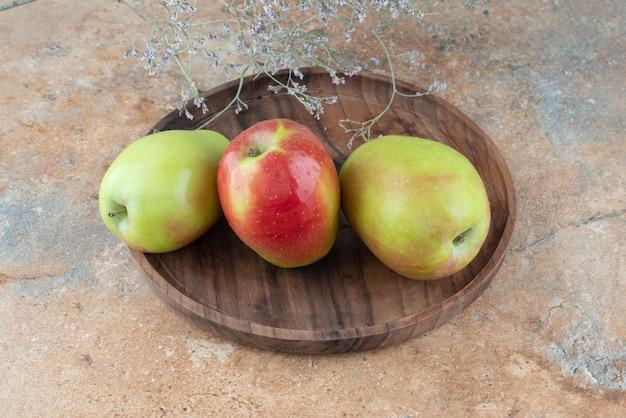 Tres manzanas frescas con flor marchita sobre plancha de madera.