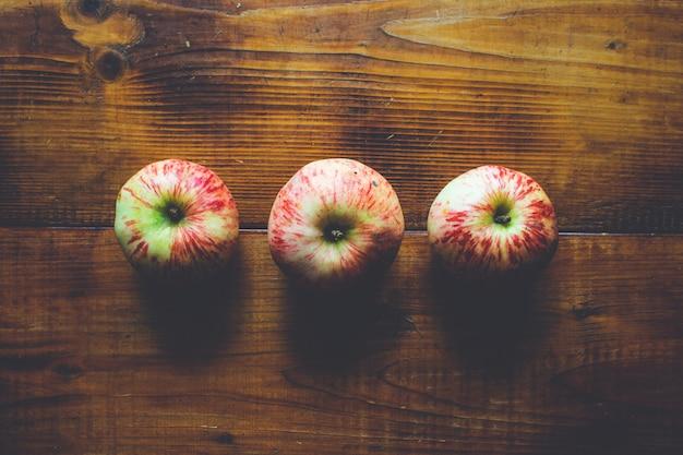 Tres manzanas maduras frescas en madera