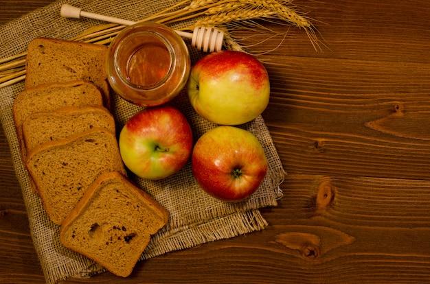 Tres manzanas, rebanadas de pan de centeno, miel, espigas en saqueo, mesa de madera