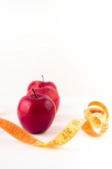 Tres manzanas rojas con cinta métrica en la mesa