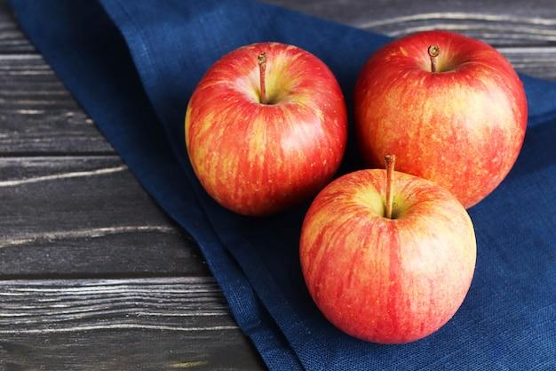 Tres manzanas rojas sobre una superficie de madera oscura.