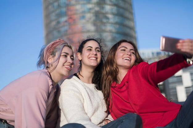 Tres mejores amigas felices al aire libre haciendo selfie en smartphone.