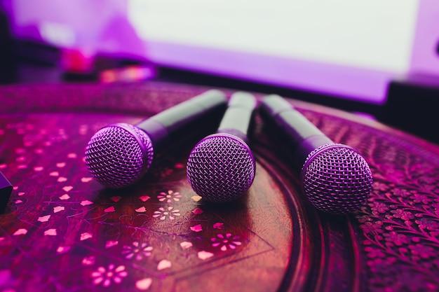 Tres micrófonos en grupo en la mesa roja con copyspace.