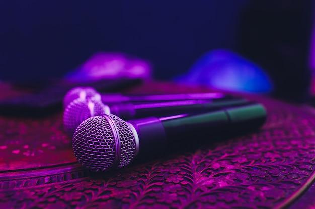 Tres micrófonos en grupo en mesa roja con espacio de copia.