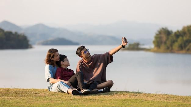 Tres miembros de la familia asiática, madre y dos hijos pequeños, sentados juntos junto al enorme lago con montañas y agua de fondo. usan teléfonos inteligentes para tomar fotos.