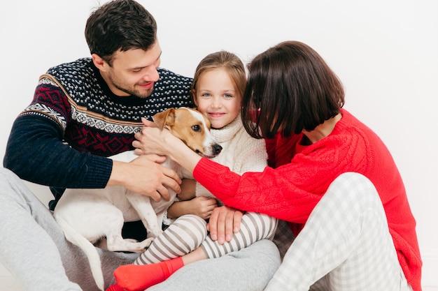Tres miembros de la familia compraron pedigree jack russell terrier dog, tienen expresiones felices