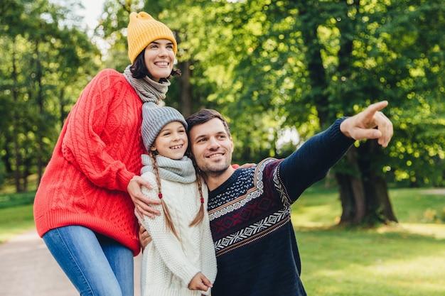 Tres miembros de la familia pasan tiempo juntos, miran el hermoso lago en el parque, indican con los dedos