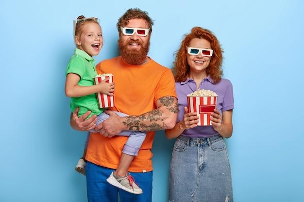 Tres miembros optimistas de la familia se ríen felices, ven comedia en el cine juntos, disfrutan comiendo deliciosas palomitas de maíz