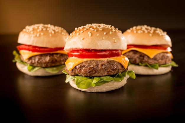 Tres mini hamburguesas en un ambiente oscuro.