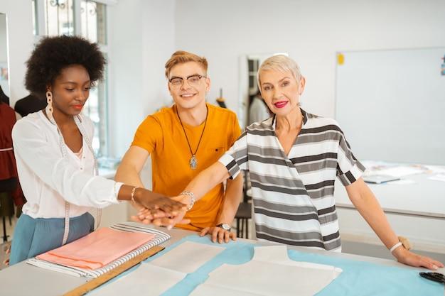 Tres modernos diseñadores de moda felices que muestran el espíritu de equipo poniendo sus manos