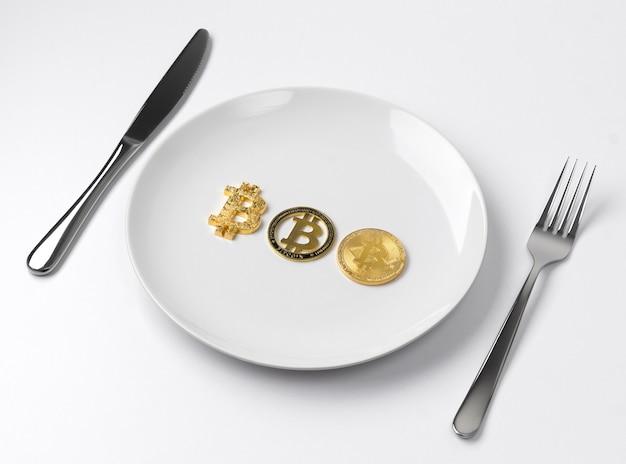 Tres monedas de oro bitcoin servido en un plato vacío blanco