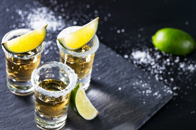 Tres montones de tequila mexicano con lima y sal