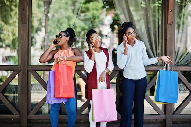 Tres muchachas afroamericanas casuales con bolsas de colores caminando al aire libre. elegante mujer negra de compras y hablando por teléfono móvil.