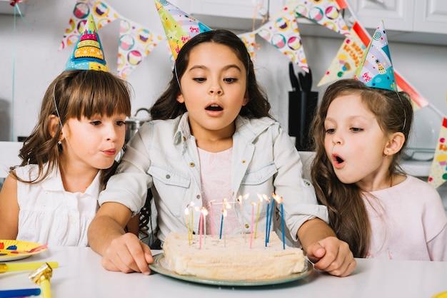 Tres muchachas bonitas que soplan velas en la torta en la fiesta de cumpleaños