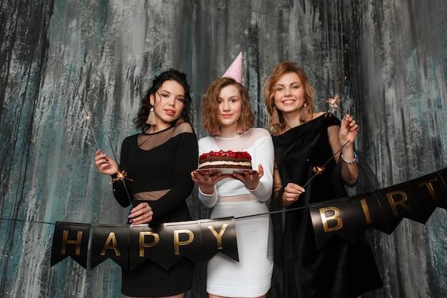 Tres muchachas hermosas jóvenes celebran el cumpleaños con pastel y bengalas