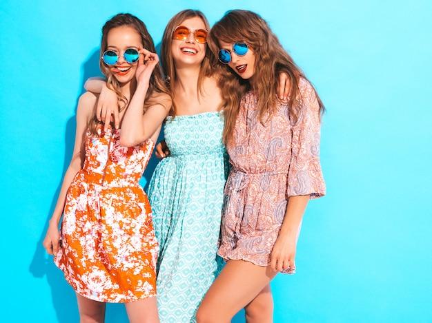 Tres muchachas sonrientes hermosas jovenes en vestidos coloridos del verano moderno. sexy mujer despreocupada en gafas de sol redondas.