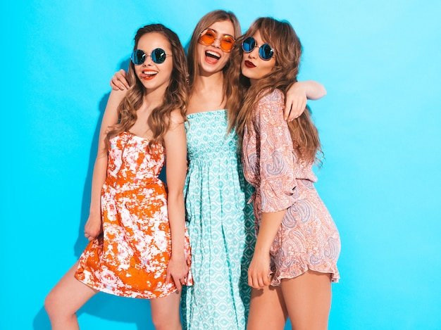 Tres muchachas sonrientes hermosas jovenes en vestidos coloridos del verano moderno. sexy mujer despreocupada en gafas de sol.