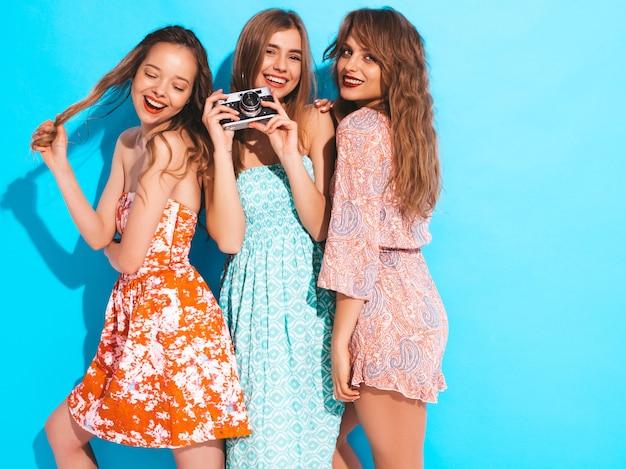 Tres muchachas sonrientes hermosas jovenes en vestidos coloridos del verano moderno. sexy mujer despreocupada posando. tomar fotos en cámara retro