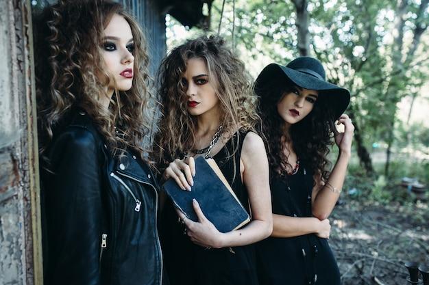 Tres mujeres antiguas como brujas, posa cerca de un edificio abandonado en vísperas de halloween