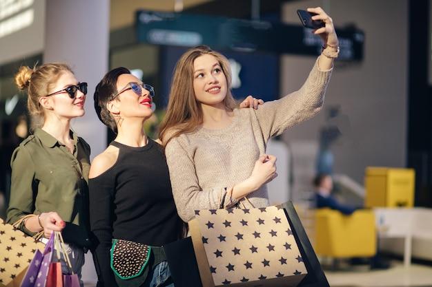 Tres mujeres con bolsas de compras tomando selfie con su teléfono inteligente