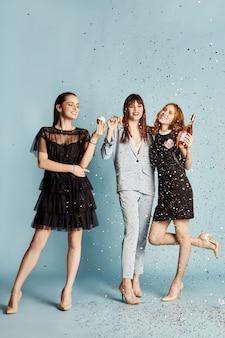 Tres mujeres celebran la fiesta divirtiéndose confeti