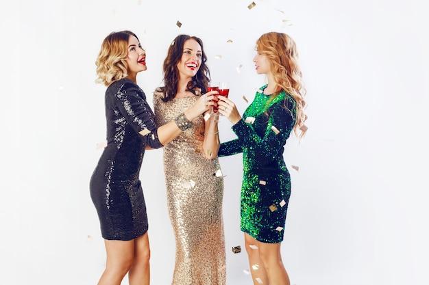 Tres mujeres celebrando en traje de noche brillante disfrutando de tiempo juntos, bebiendo vino y bailando. fondo blanco.