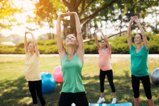 Tres mujeres embarazadas y su entrenador en un yoga en el parque.