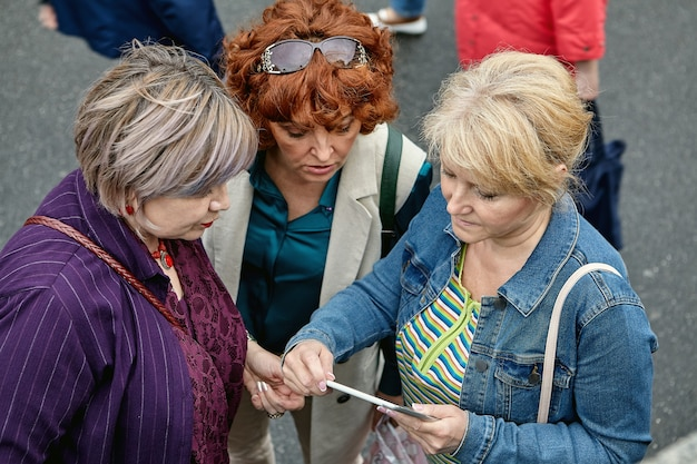 Tres mujeres europeas mayores hablando en la calle, vista superior.