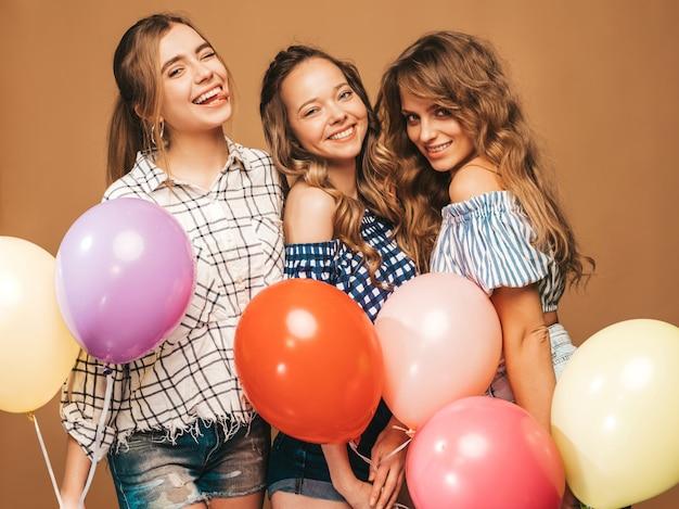 Tres mujeres hermosas sonrientes en ropa de verano camisa a cuadros. chicas posando modelos con globos de colores. divirtiéndose, listo para celebrar cumpleaños