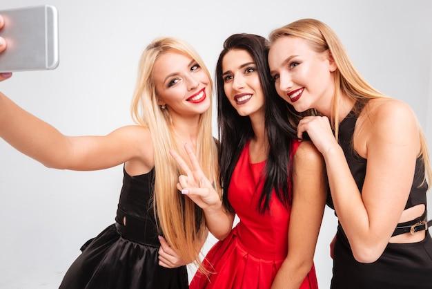 Tres mujeres jóvenes alegres haciendo selfie con teléfono celular sobre fondo blanco.