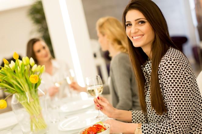 Tres mujeres jóvenes brindando con vino blanco