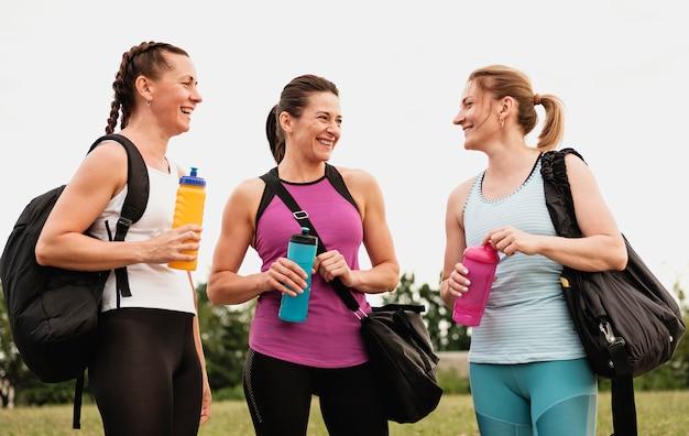 Tres mujeres jóvenes en forma saludable de pie charlando